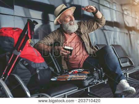 Cheerful old tourist is sitting in airport and looking ahead with bright smile. He holding small book. Copy space on left side
