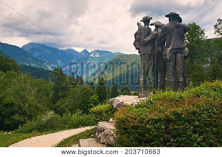 Ribcev Laz, Slovenia - July 4, 2017: Town park close to Bohinj Lake with the Monument To Four Courageous Men that climbed highest mountain Triglav in Slovenia in 1778.