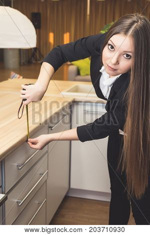 Young woman with long hair measures the height of a ruler in the kitchen, looks at the camera
