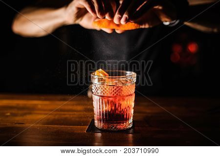 bartender with cocktail and orange peel preparing cocktail at bar. alcohol drinks people and luxury concept