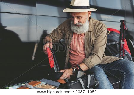 Mature bearded tourist is packing his luggage. He sitting on chair in waiting hall. Copy space on left side
