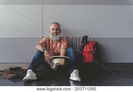 Cheerful mature tourist is holding hat like asking for money and looking at camera with bright smile. He sitting on floor. Portrait. Copy space on right side