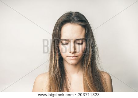 Portrait of a young frustrated woman with long hair, she looks down