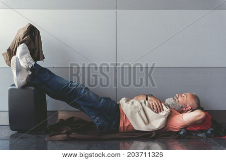 Relaxed mature bearded tourist is closing his eyes and lying on floor. He putting legs on luggage. Copy space