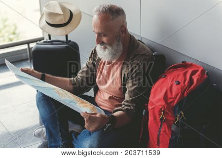 Joyous mature bearded man sitting on floor and reading unfolded map. His luggage near him. Copy space on right side