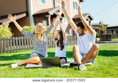 Upsurge of joy. Happy lovely family sitting on the lawn in their backyard and raising hands up, cheering happily