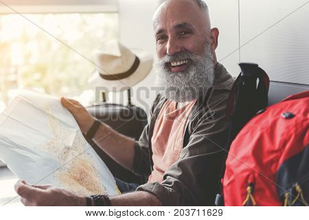 Joyous mature bearded man is using man and looking at camera with smile. He sitting in waiting hall. Portrait. Copy space on left side