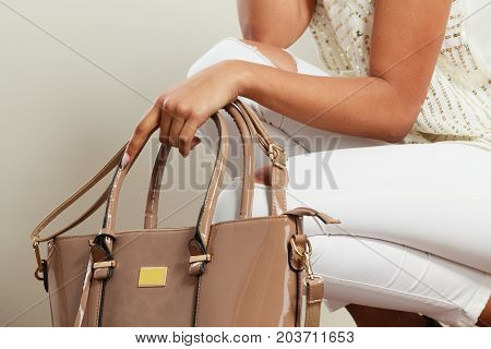 Fashion concept. Clothing and accessories. Woman hands holding beige handbag. Lady in white clothing with lacquered leather bag.