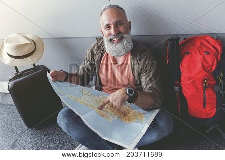 Glad mature bearded tourist is sitting near wall and pointing on certain place at unfolded map. Male person looking at camera with smile. Portrait. Top view