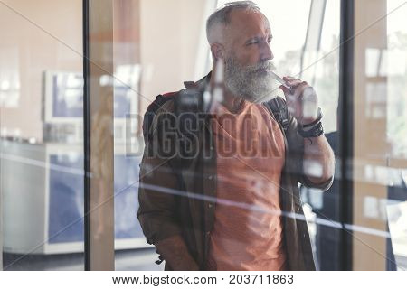 Pensive old tourist is smoking and thoughtfully looking aside. He standing behind transparent glass wall at airport. Profile. Copy space on left side