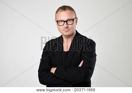 Smiling young man in black clothes standing with crossed hands against white background Concept of self confident man. Positive man emotion