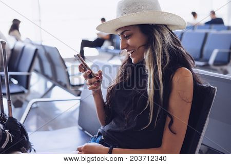 Airport woman in hat on smart phone at gate waiting in terminal. Air travel concept.Looking something in mobile,use  app