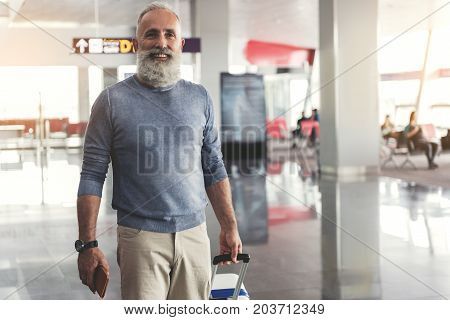 Glad bearded mature tourist is standing in waiting hall and looking ahead with bright smile. He holding necessary documents. Waist up portrait. Copy space on right side
