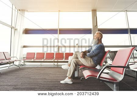 Cheerful bearded mature tourist is sitting on chair and looking at window of airport. Profile. Copy space on left side