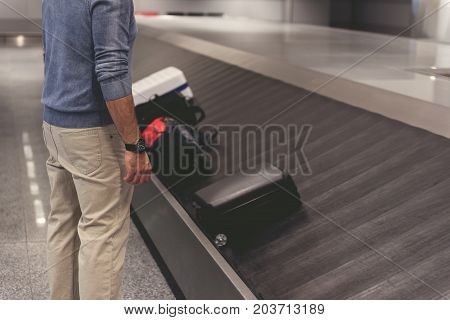Tourist is standing nearby baggage tape in airport and waiting for his case. Focus on male person. Copy space on right side