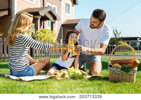 Cheers to us. Lovable young family enjoying picnic in their backyard and clinking glasses with orange juice