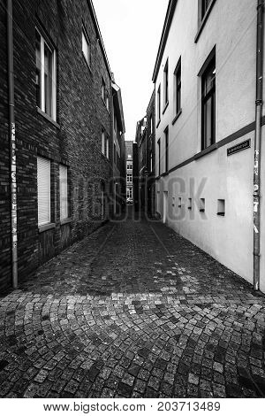 MAASTRICHT NETHERLANDS - JANUARY 09 2015: Old narrow street in the historic center. Black and white. Maastricht is the oldest city of the Netherlands and the capital city of the province of Limburg.