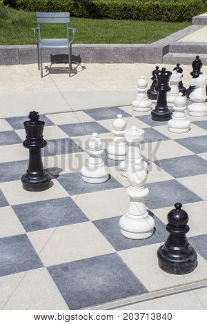 Street chessboard with one chair and green grass as background