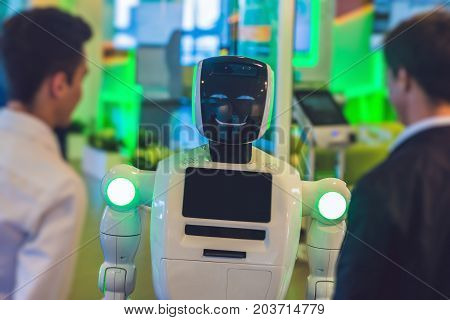 Two Men Talking With A Robot. Chatbot Concept. Social Media Mesh And Futuristic Design