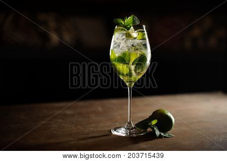 Mojito cocktail with lime and mint in highball glass on a dark stone background Copy space