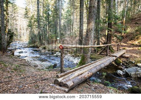 Wooden log footbridge crossing a pure mountain river in the forest with a blaze drawn for direction. Wilderness nature preservation clean water and environmental conservation concept.