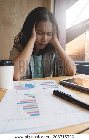 Stressed of Asian Business woman having headache from overtime working with tablet pen documents and cup of coffee at the office.