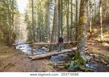 Woman hiker crossing a footbridge in forest across a pure mountain river with a blaze drawn for direction sun shining. Active lifestyle pristine nature concept.