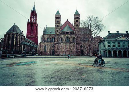 MAASTRICHT NETHERLANDS - JANUARY 09 2015: Vrijthof square. Evangelical Church of John the Baptist (left) and the Basilica of Saint Servatius (right). Vintage toning. Stylization.