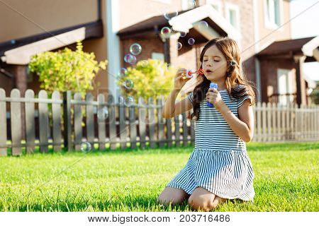 Summertime hobby. Beautiful little girl sitting on the grass near her house and blowing soap bubbles
