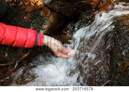 Thirsty hiker drinking water from a crystal clear stream in the mountains. Adventure fundamental right to water back to nature and natural lifestyle concept.