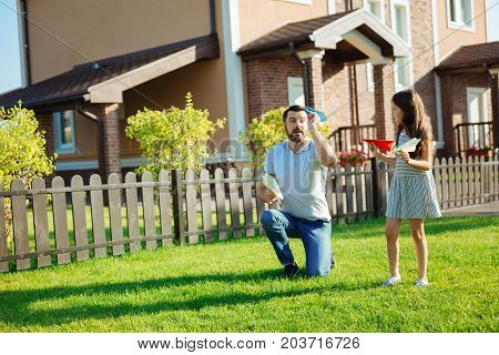 Role model. Pleasant loving father showing his beloved little daughter how to launch paper planes while playing with her in the backyard