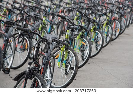 A row of a large number of bicycles with black wheels on the town square in summer