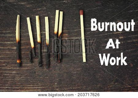 Burnt matches on the wooden tablle and text Burnout At Work