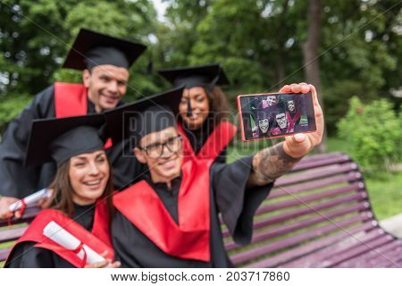 Lets safe this moment forever in our memory. Cheerful young students are making selfie while showing their diplomas to camera. They are sitting on bench and laughing. Focus on smartphone screen