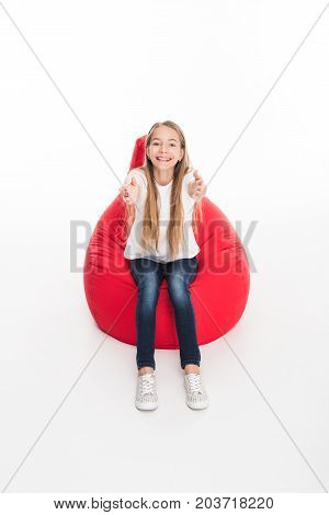 adorable smiling female youngster sitting in red bean bag chair isolated on white