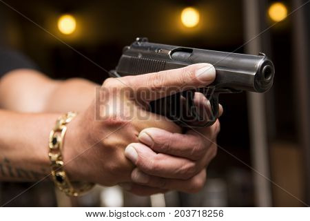 Black Gun In The Hands. Hands Aiming With A Gun