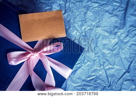 The Dark blue gift box with ribbon decoration on polka blue paper Happy Father's Day or celebration gift concept top view and overhead shot right copy space background