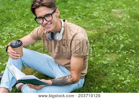 Portrait of cheerful young man coffee while reading literature. He is wearing headphones on neck. Guy is looking at camera and smiling while relaxing on green grass