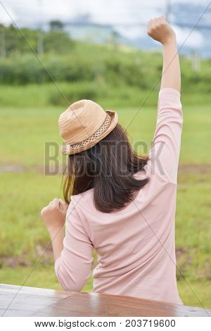 Rear view. Happy Relaxed Asian woman wear hat. Outstretched arms on green natural background in the morning. Resting on Holiday.