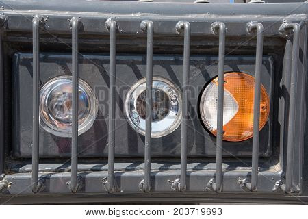 Signal headlamp protected by a metal grating from a heavy truck for industrial purposes