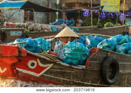 CAN THO VIETNAM - 3/24/2016: A merchant waits for customers at Cai Rang Floating Market on the Mekong river.