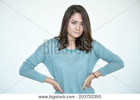 Portrait of young tender woman. She is angry and looks in camera with doubt. Negative facial expression