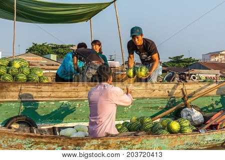 CAN THO VIETNAM - 3/24/2016: A merchant sells watermelon to a re-seller at Cai Rang Floating Market on the Mekong river.