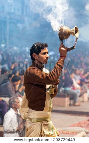 VARANASI, INDIA - JANUARY 3, 2016: Indian Brahmin conducts religious Ganga Maha Aarti ceremony (fire puja) at Dashashwamedh Ghat