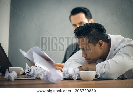 Worried businessman in dark suit sitting at office desk full with books and papers being overloaded with work. Vintage effect style pictures.