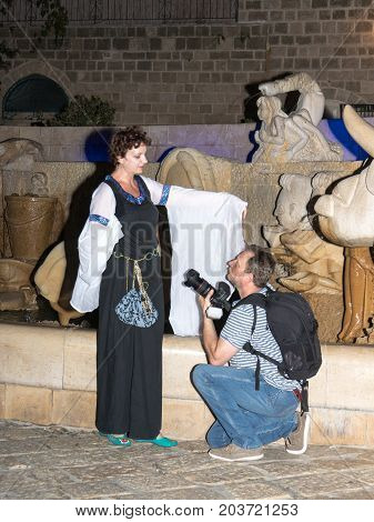 Tel Aviv-Yafo Israel September 08 2017: The photographer knelt before the girl - a member of the Knights of Jerusalem club dressed in the traditional costume of a medieval lady at night in the old town of Yafo in Tel Aviv-Yafo Israel