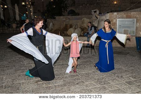 Tel Aviv-Yafo Israel September 08 2017: Two girls - of the Knights of Jerusalem club dressed in traditional costumes of medieval ladies dance with a girl at night near the fountain in the old town of Yafo in Tel Aviv-Yafo Israel