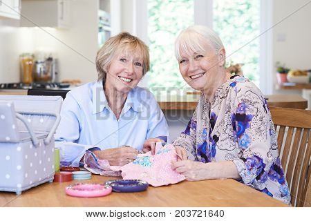 Portrait Of Two Senior Women Sewing Quilt Together
