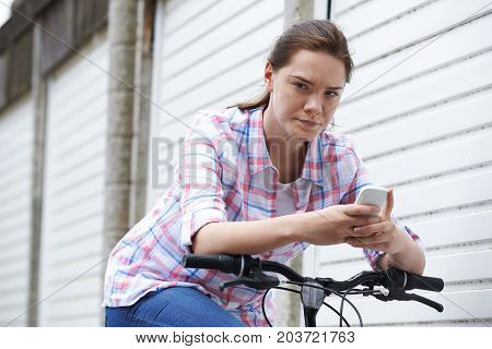 Portrait Of Teenage Girl On Bike Texting Using Mobile Phone