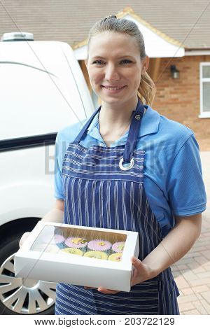 Female Baker Standing Next To Van Making Home Delivery Of Cupcakes